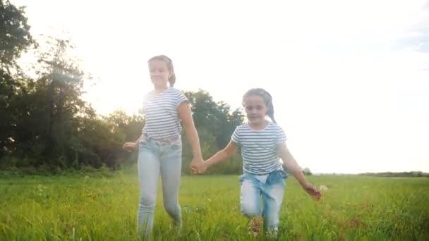 šťastné rodinné děti spolu běhají v parku při západu slunce. lidé v konceptu parku. dvě sestry radostně utíkají. šťastná rodina a malé dítě zábava léto dítě životní styl sen koncept