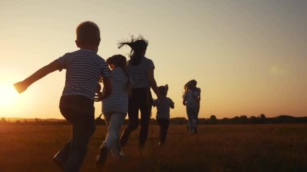 děti šťastné rodinné dítě spolu běhají v parku při západu slunce silueta. lidé v konceptu parku. Matka dcera a syn radostně utíkají. šťastná rodina a malé dítě zábava léto dítě sen koncept