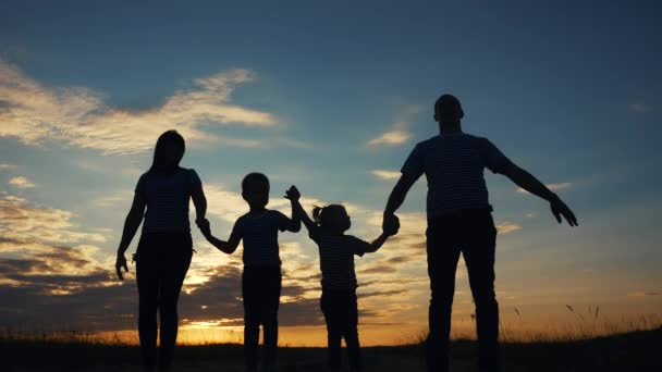 happy family raise their hands up in the park silhouette. family friendly kid dream concept. happy family parents holding hands raised their hands up. dad mom daughter and son dream are happy in park