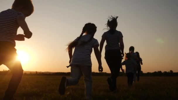 children happy family kid together run in the park at sunset silhouette. people in the park concept. mom daughter and son joyful run. happy family and little fun baby child summer kid dream concept