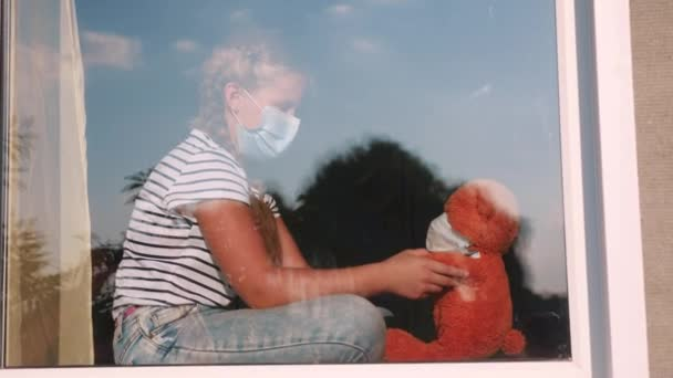 bored kid in medical mask in home quarantine coronavirus sitting by the window. child with a covid 19 toy teddy bear in protective mask looking out the window. coronavirus epidemic prevention concept