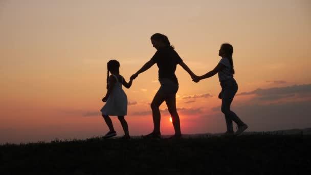 šťastné rodinné procházky při západu slunce v parku siluette.mom a dvě dcery držet ruce venku. koncepce dětských snů. Šťastná rodinná procházka. matka a malé děti životní styl procházky v parku