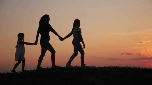happy family walks at sunset in the park silhouette.mom and two daughters hold hands outdoors. kid dream concept. happy family walk lifestyle together. mother and little children walking in the park