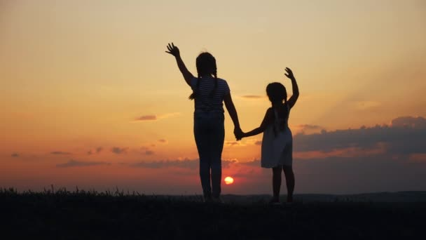 happy family two sisters sunset walks at in the park silhouette say goodbye waving hand. two daughters. kid dream concept. happy sunset family walk together. children travel kid walking in the park