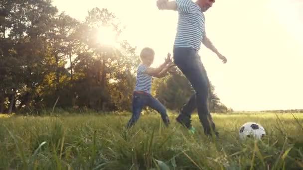 otec a syn hráli fotbal v parku na trávě. Šťastný rodinný sen dítě koncept. táta a kluk hrát míč venkovní sporty v parku zdravé. rodiče hraje se synem do životního stylu míč