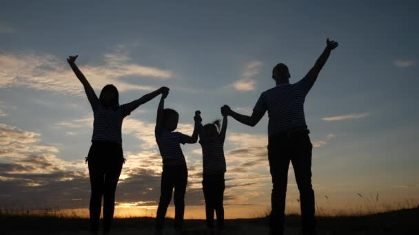 happy family raise their hands up in the park silhouette. family friendly kid dream concept. happy family parents holding hands raised their hands up. dream dad mom daughter and son are happy in park