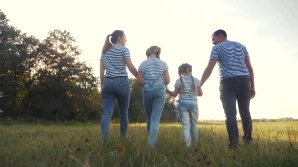 šťastnou rodinnou procházku v parku. přátelské rodinné dítě sen koncept. Máma táta a děti chodí do parku na zelené trávě venku. šťastná rodina se zády chůze životní styl v parku v