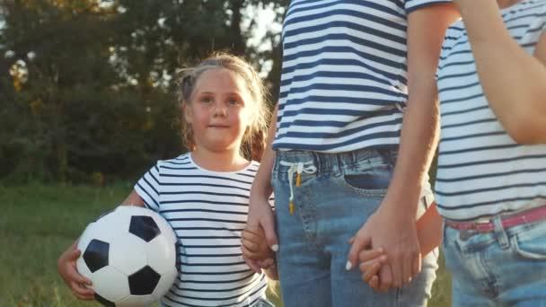 šťastné rodinné děti s mámou hrají fotbal v parku. koncepce dětských snů. Ten kluk hraje míček na zelené trávě v parku. šťastná rodina maminka se zábavou děti procházky hrát v parku na trávě