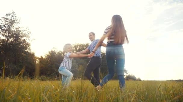glückliche Familie Mama Papa und Tochter spielen Reigen. Menschen im Park-Kind-Traum-Konzept. glückliche Familieneltern mit kleinem Kind Tochter spielen im Park auf dem Gras und halten Lifestyle-Hände