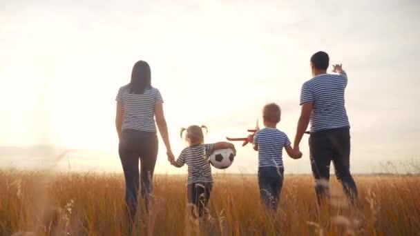 fröhlicher Familienspaziergang im Sommerpark. kindertraumfreundliches Familienkonzept. Kinder spielen mit Ball und Spielzeugflugzeug. glückliche Familieneltern gehen mit Kindern im Park spazieren. Kinder spielen Flugzeug Spaß Traum