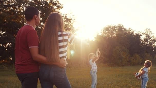 šťastná rodina v parku, jak si hraje s míčem. dítě snít společně koncept. děti házejí míč v parku na trávě venku. dívka a šťastná rodina hraje na dovolené zábavné cestování