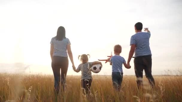 šťastnou rodinnou procházku v letním parku. dětský sen přátelský rodinný koncept. děti si hrají s míčkem a letadlem. šťastní rodinní rodiče chodí s dětmi do parku. dítě hrát zábavné letadlo sen