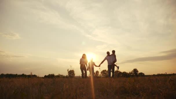 šťastné rodinné děti se společně procházejí v parku při západu slunce silueta. lidé v konceptu parku máma táta dcera a životní styl sestra radostná procházka. rodiče a malé dítě zábava léto