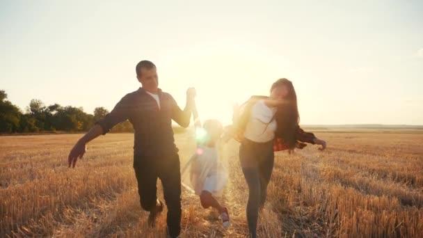 Ein glücklicher Familienbetrieb auf dem Feld wirft seine Tochter um. Kindertraum-Konzept. Tochter und Eltern rennen über ein Weizenfeld in der Nähe des Parks. glücklicher Lebensstil der Familie Traum vom Glück. Kind und Eltern laufen