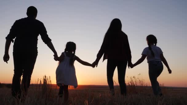 lidi v parku. šťastná rodinná silueta při západu slunce. Máma táta a dcery chodí a drží se za ruce v parku. koncepce snů šťastných rodinných dětí. rodiče a děti kráčející zpět silueta zábava
