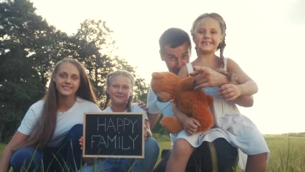 happy family looks at the camera in the park on green grass. dream family concept. kid and parents happy family waving hand to camera in the park. family mom dad lifestyle and daughters hug together