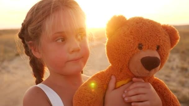 Egy kislány, aki egy plüssmacis portrét ölelget a parkban a természetben. gyermekkori álom életmód koncepció. mosolygós gyerek gyermek kedvenc játék Teddy maci álom a boldogság egy zöld szabadtéri parkban
