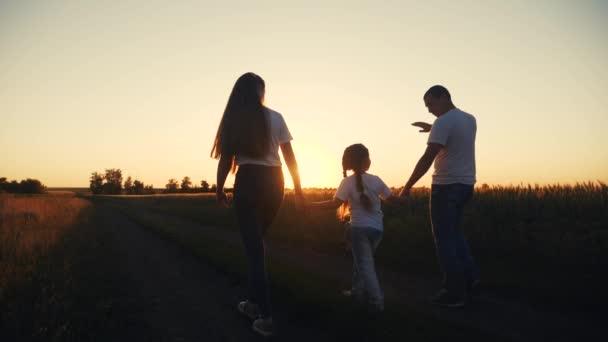 šťastná rodina se za soumraku vydá na procházku do parku na siluetu. dcera drží mámu a. lidé v konceptu parku. otec otec matka rodiče a malé dítě joint procházky v terénu. málo