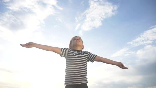 A fiú imádkozik, hogy húzza a kezét, és élje az eget a kék ég felé. gyermek koncepció hit vallás és boldog család. A fiú oldalra teszi a kezét a kék égi zsidó ellen, aki Istenhez imádkozik. imádat és hála