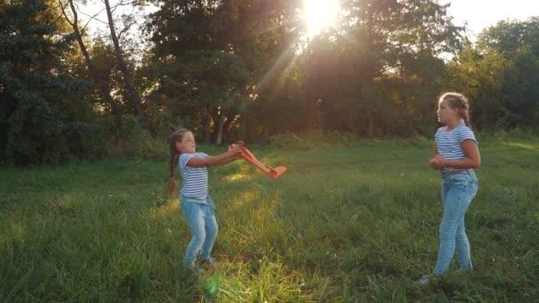 A gyerekek játékgéppel játszanak a parkban. boldog család gyerek álom szabadság repülőgép egy koncepció. gyerekek játszanak a parkban dobja a gépet. gyerek lány játszik szórakoztató játék repülőgép szabadban álom