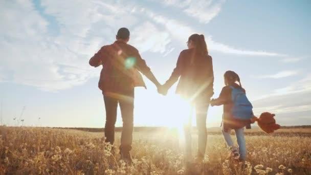 šťastnou rodinnou procházku v parku. přátelské rodinné dítě sen koncept. Máma táta a dítě procházka v parku na zelené trávě venku. šťastný životní styl rodiny s jejich zády procházky v parku