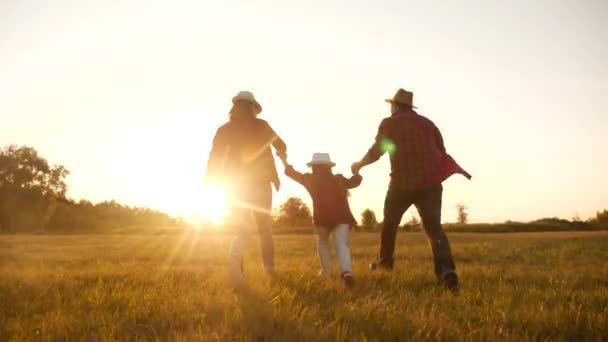 Šťastné rodinné dítě běží v parku při západu slunce. lidé v konceptu parku máma táta dcera a syn radostný běh. šťastná rodina a malé dítě zábava léto dítě sen silueta koncept