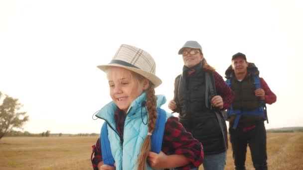 šťastní rodinní turisté chodí na túry do parku. Týmová práce. dobrodružství cestování činnosti koncept. šťastní rodinní turisté s batohy turisté jít kempovat. skupina lidí v parku chůze venkovní týmová práce