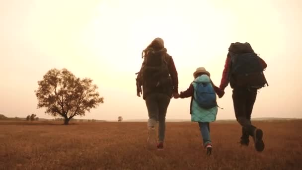 šťastní rodinní turisté běží v parku s batohy. Týmová práce. dobrodružství cestování činnosti koncept. šťastní rodinní hackeři se drží za ruce. turisté běží v divokém venkovním parku