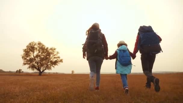 šťastní rodinní turisté běží v parku s batohy. Týmová práce. dobrodružství cestování činnosti koncept. šťastní rodinní hackeři se drží za ruce. turisté běží ve volné přírodě parku