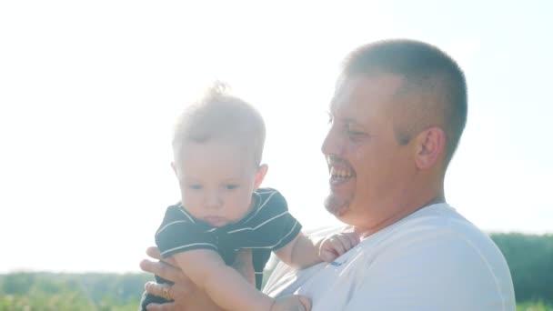 Apa csók tartja a kisfiút a karjaiban játszik a parkban. Apa nap gyerek álom gyermekkor boldog családi koncepció. A szülő kézen fogva játszik egy kisfiú napfényével. emberek a parkban boldog család