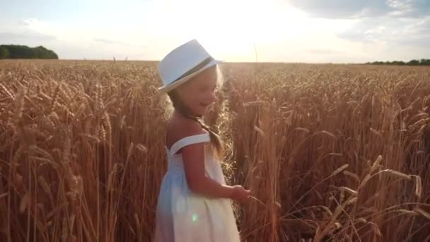 kid little girl walking on a wheat field. happy childhood dream family concept. baby daughter in a white hat and dress walks through a wheat field view from the back lifestyle. agriculture harvesting