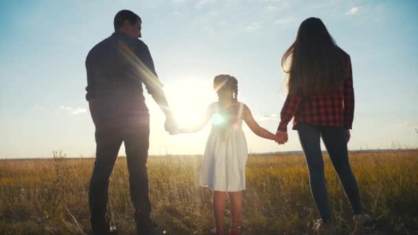 glückliche Familieneltern halten ihre Tochter an der Hand. Mutter und Mädchen Hand in Hand bei Sonnenuntergang. Eltern und Kind halten Händchen. glücklich Spaß Familie Muttertagskonzept