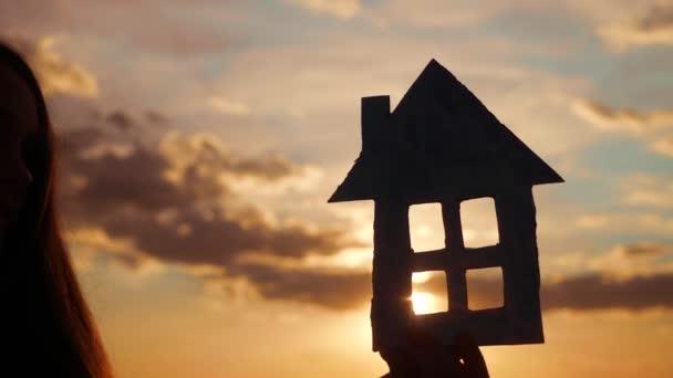 Papierhaus in der Hand Silhouette bei Sonnenuntergang. Versicherungshypothek Eigenheimmarkt Konzept. handgeschöpftes Papierhaus in der Sonne am Sonnenuntergang. Traum vom Eigenheim als Symbol