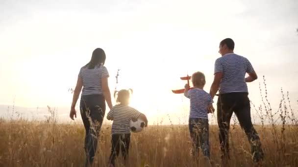 šťastnou rodinnou procházku v letním parku. dětský sen přátelský rodinný koncept. děti si hrají s míčkem a letadlem. šťastní rodinní rodiče chodí s dětmi do parku. dětská zábava hrát letadlo sen