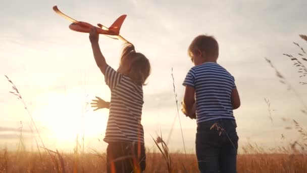 happy kids childs walk with airplane a in the park. kid silhouette play plane. happy family dream freedom airplane concept. kids walk on wheat field fun at sunset holds in his hands dream toy aircraft