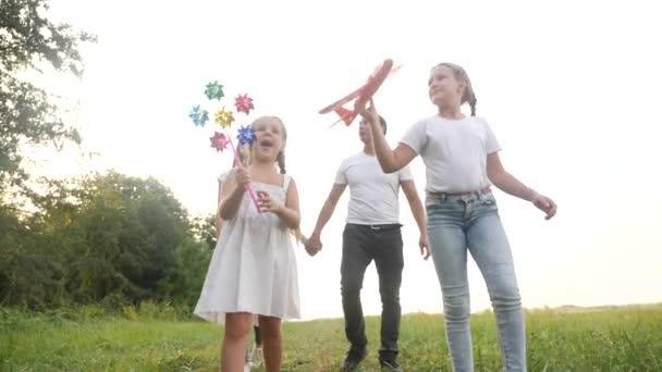 šťastnou rodinnou procházku v letním parku. dětský sen přátelský rodinný koncept. Děti si hrají s kuličkovým a hračkovým letadlem. šťastní rodinní rodiče chodí s dětmi do parku. dítě hrát letadlo sen zábava