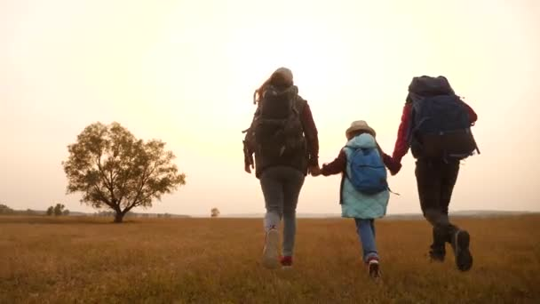 šťastní rodinní turisté běží v parku s batohy. Týmová práce. dobrodružství cestování činnosti koncept. šťastní rodinní hackeři se drží za ruce. turisté běží v přírodě divoký park