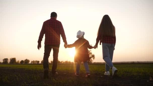 šťastnou rodinnou procházku v parku silueta. přátelské rodinné dítě sen koncept. šťastná rodina, jak se při západu slunce drží za ruce v parku. přátelský rodinný venkovní sen spolu