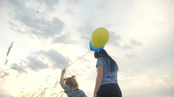 Menschen im Park. glückliche Familie Tochter und Mutter spazieren in mit Luftballons Silhouette Teamwork Geburtstagsparty bei Sonnenuntergang. Das Konzept einer glücklichen Familie, die zusammenlebt. glückliche Familie zu Fuß Kind
