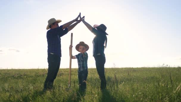 Die Silhouette des glücklichen Familienvaters Sohn und der Mutter zeigt ein Haus und ein Trostsymbol bei Sonnenuntergang. glückliche Familie Eltern Mutter und Vater und Kind Lebensstil Kinder porträtieren Hausdach halten ihre Hände