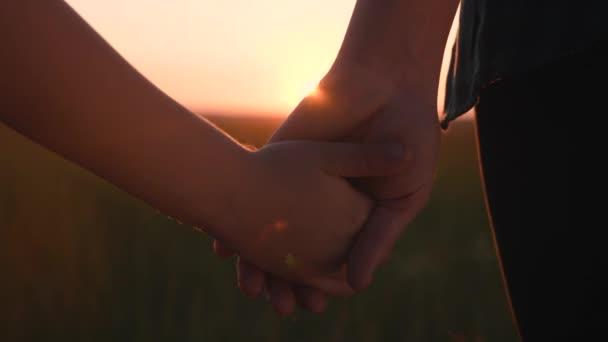 Glückliche Familienmütter und -söhne halten Händchen. Mutter und Junge Hand in Hand bei Sonnenuntergang. Eltern Mädchen und Kind Lebensstil glückliche Kindheit
