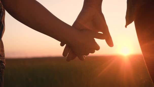 Glückliche Familienmütter und -söhne halten Händchen in Teamarbeit. Mutter und Junge Hand in Hand bei Sonnenuntergang. Eltern Mädchen und Kind glückliche Lebensstil Kindheit. Glückliches Familienmuttertagskonzept