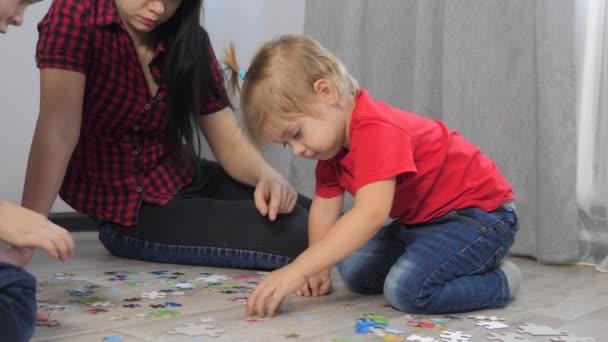 Dcera holčička šťastná rodinná sbírka hádanky týmová práce. rozvoj životního stylu jemné motorické dovednosti a myšlení. dcera a dívka s maminkou sbírat mozaiky puzzle