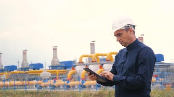 Konzept für die Förderung von Erdöl und Erdgas im Bergbau. Ingenieurskraft und Energie mittels digitaler Tablets. Arbeiter mit Helm bei Arbeiten in einer Ölgasanlage. Lifestyle-Ingenieur studiert Wirtschaftswissenschaften