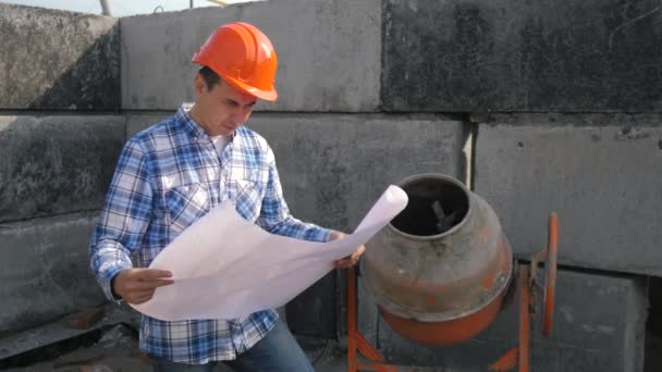 male architect builds a foundation of cement. concept building constructing architect slow motion video. man builder study with the house paper plan. architect working on lifestyle construction of
