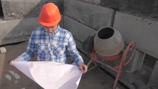 male architect builds a foundation of cement. concept building lifestyle constructing architect slow motion video. man builder study with the house paper plan. architect working on construction of