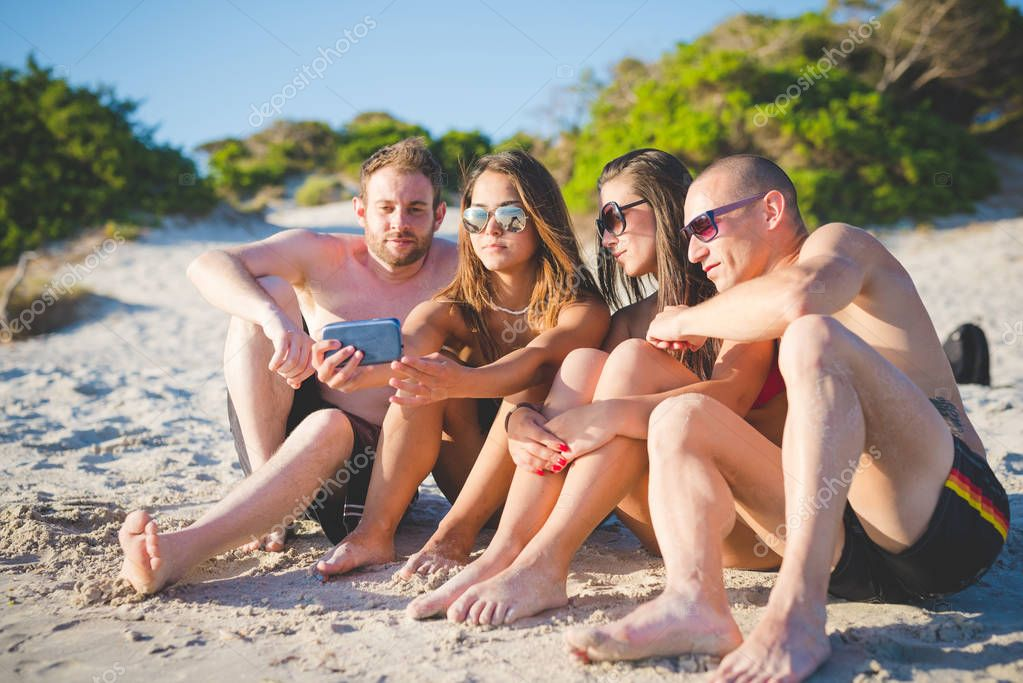 Group of friends millennials using smartphone taking selfie