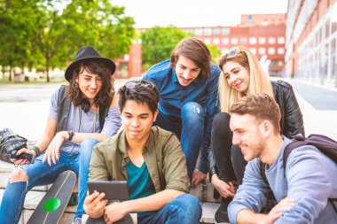 group of friends multiethnic sitting outdoor using smartphone streaming online