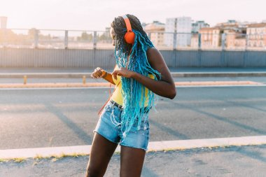 young black millennial woman outdoor listening music dancing - freedom, woman power, happiness concept