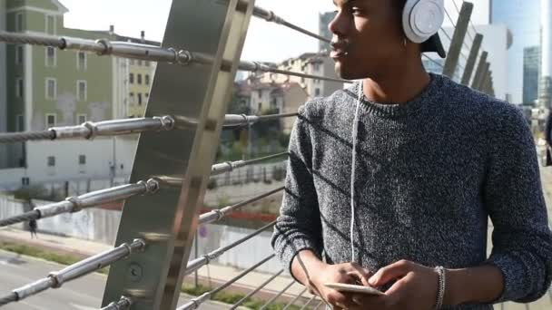 Young handsome american african man listening music with headphones and smartphone in city in back light city